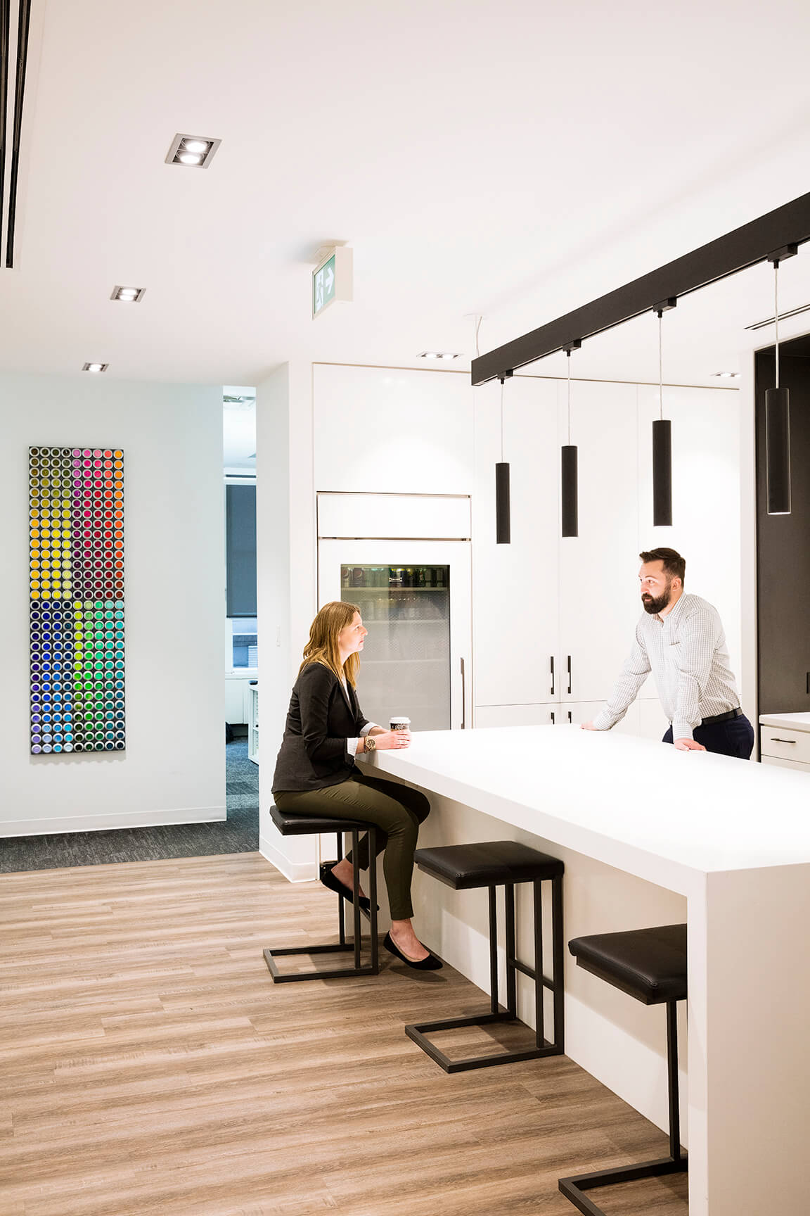 An architect and a designer chat over a long, high table with black, high chairs in the kitchenette at Zeidler's office in Calgary.